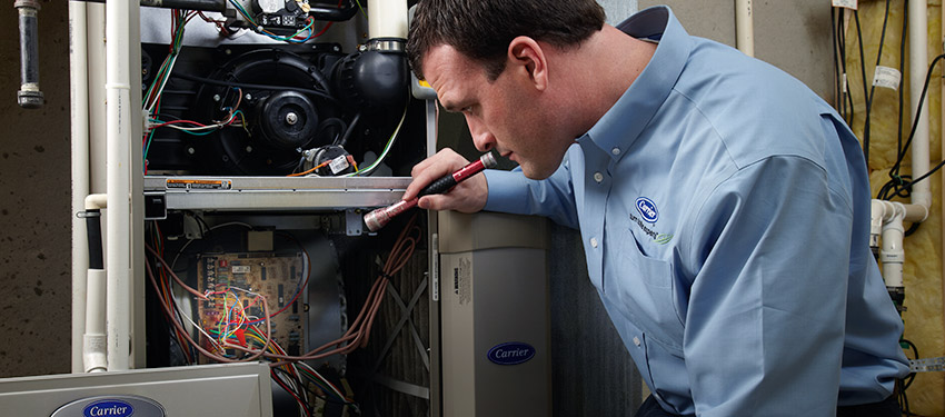 An HVAC technician performing furnace maintenance